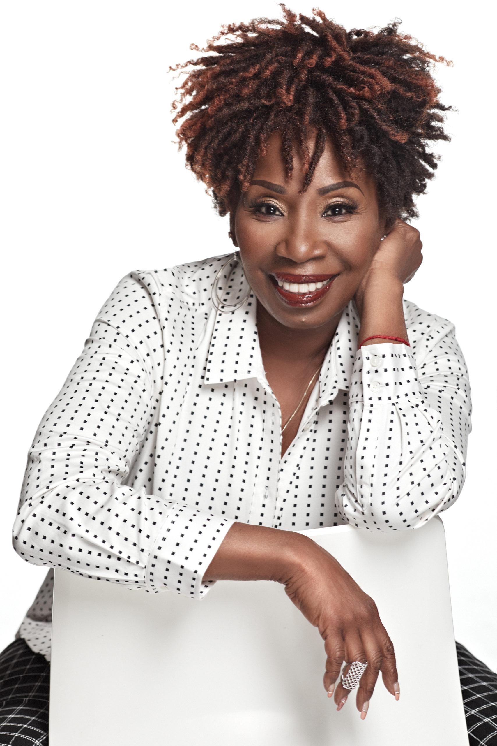Iyanla Vanzant sitting and smiling in white polka dotted shirt